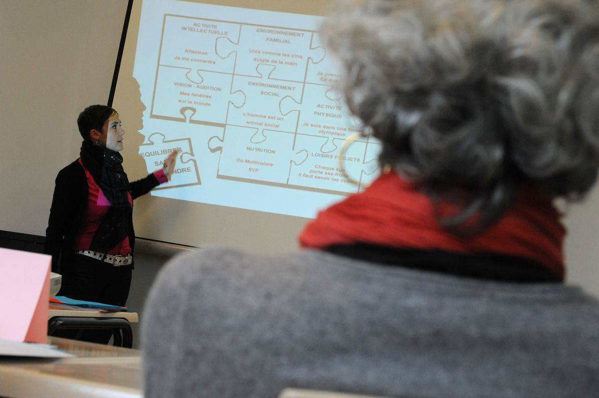An elderly woman watches a lecturer teach a class about memory.