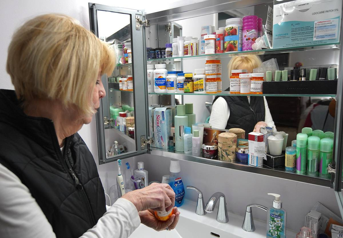 A woman packs medications from her restroom's medicine cabinet.