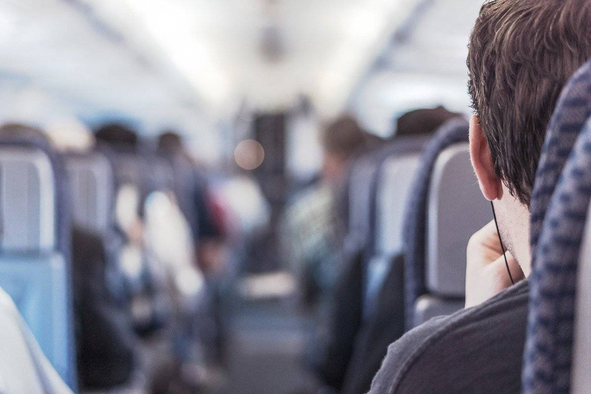 An airplane passenger sits on an aisle seat.