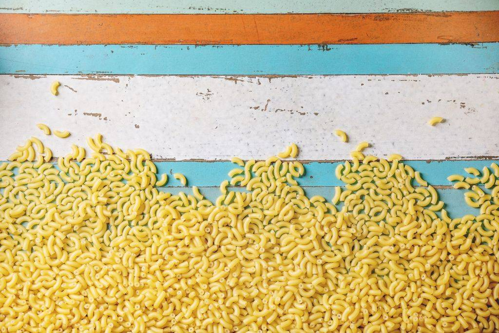 Heap of raw uncooked italian pasta coquillettes over blue wooden plank background