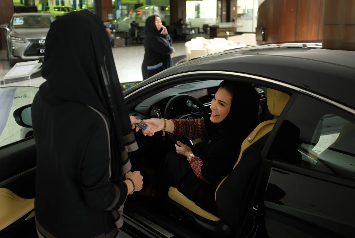 A customer receives car keys for a rented car in Saudi Arabia.
