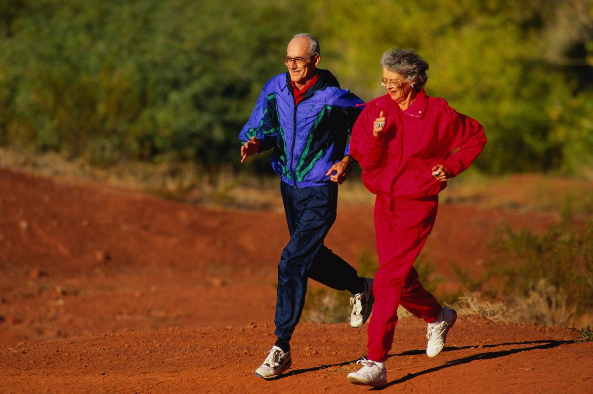 Two elderly adults run together.