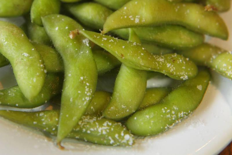 A plate has salted edamame.