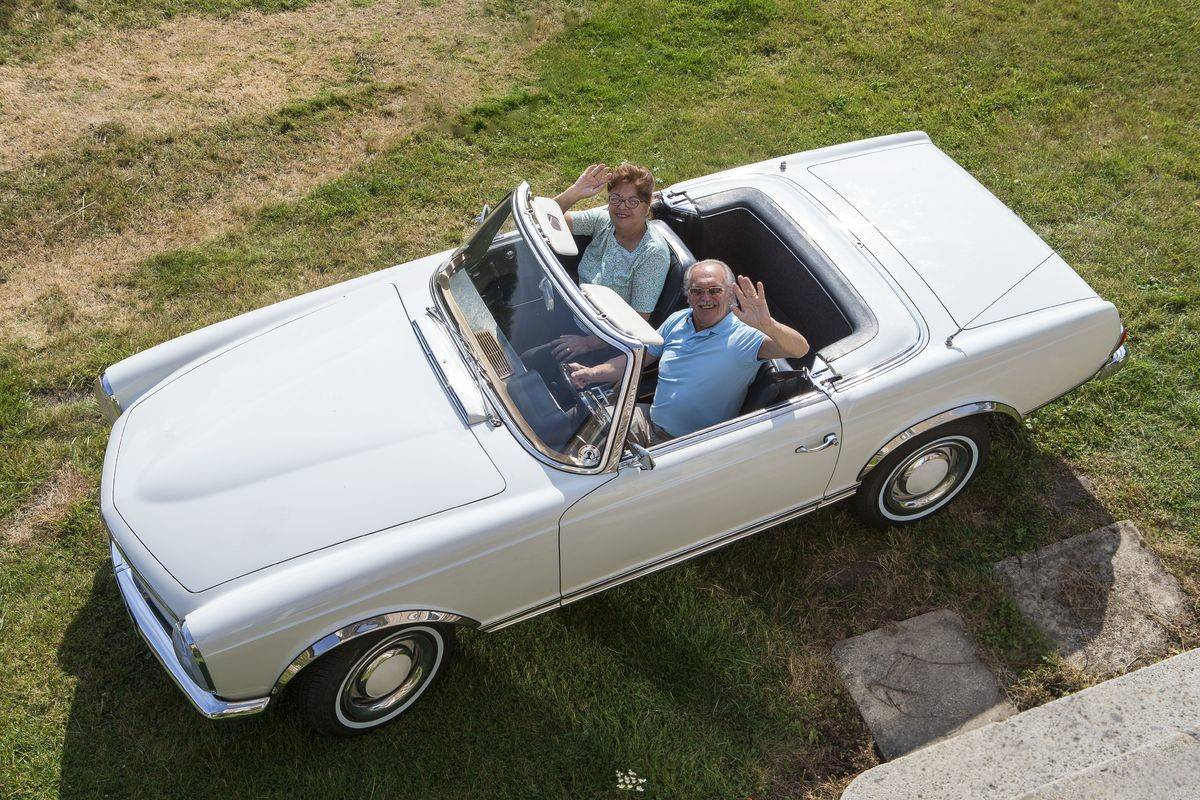 A senior couple waves to the camera from a convertible.