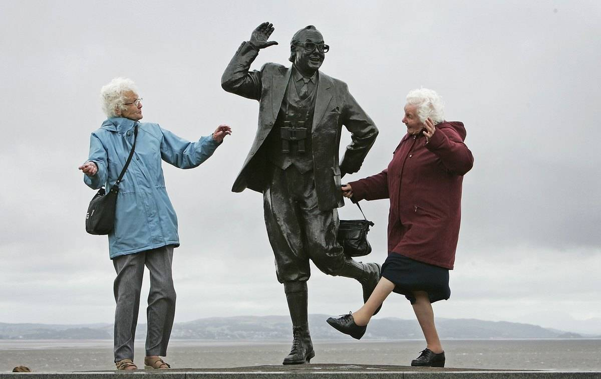 Two senior women perform a famous comedic dance next to a statue of Eric Morcambe.