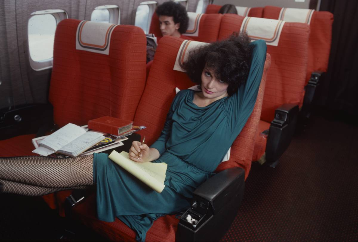 A designer lounges in a plane seat while writing.