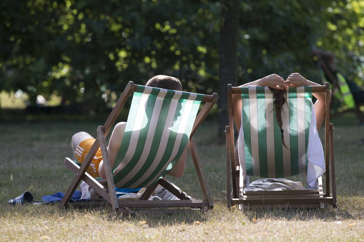 Two women relax in lounge chairs outside.