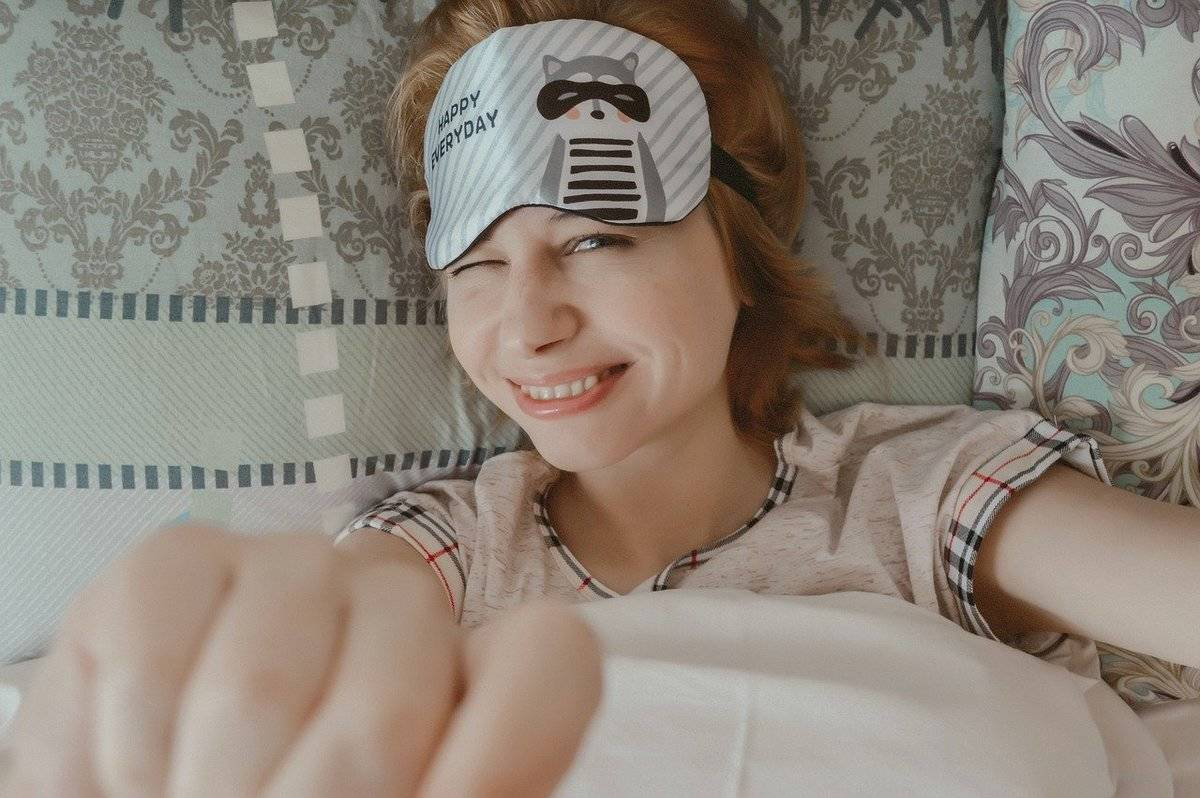 A woman smiles as she goes to bed in her pajamas and eye mask.
