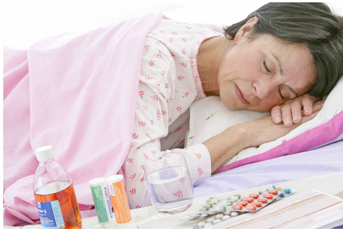 An elderly woman sleeps next to medications on the table.