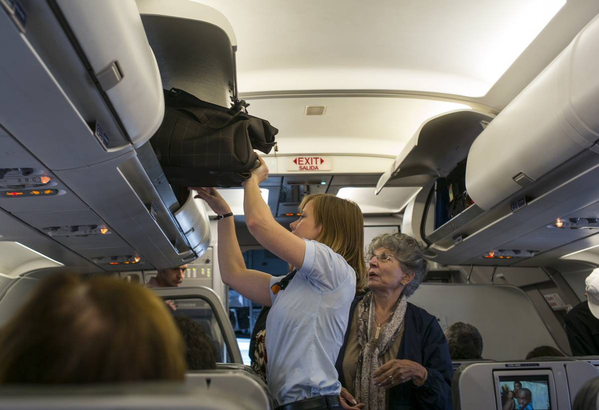 A flight attendant helps an elderly passenger lift her carry-on bag into the compartment.