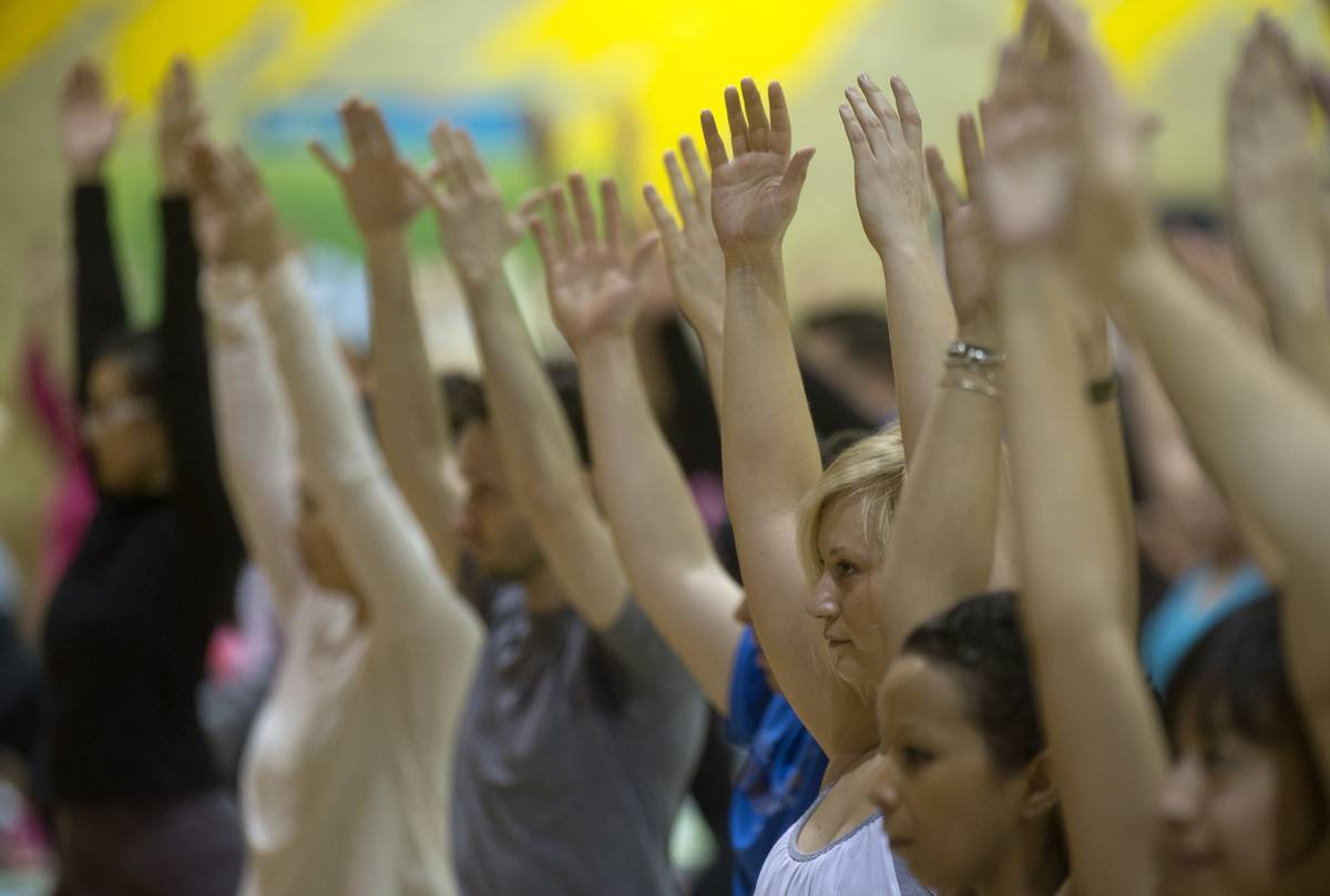 During an exercise class, people raise their arms into the air to stretch.