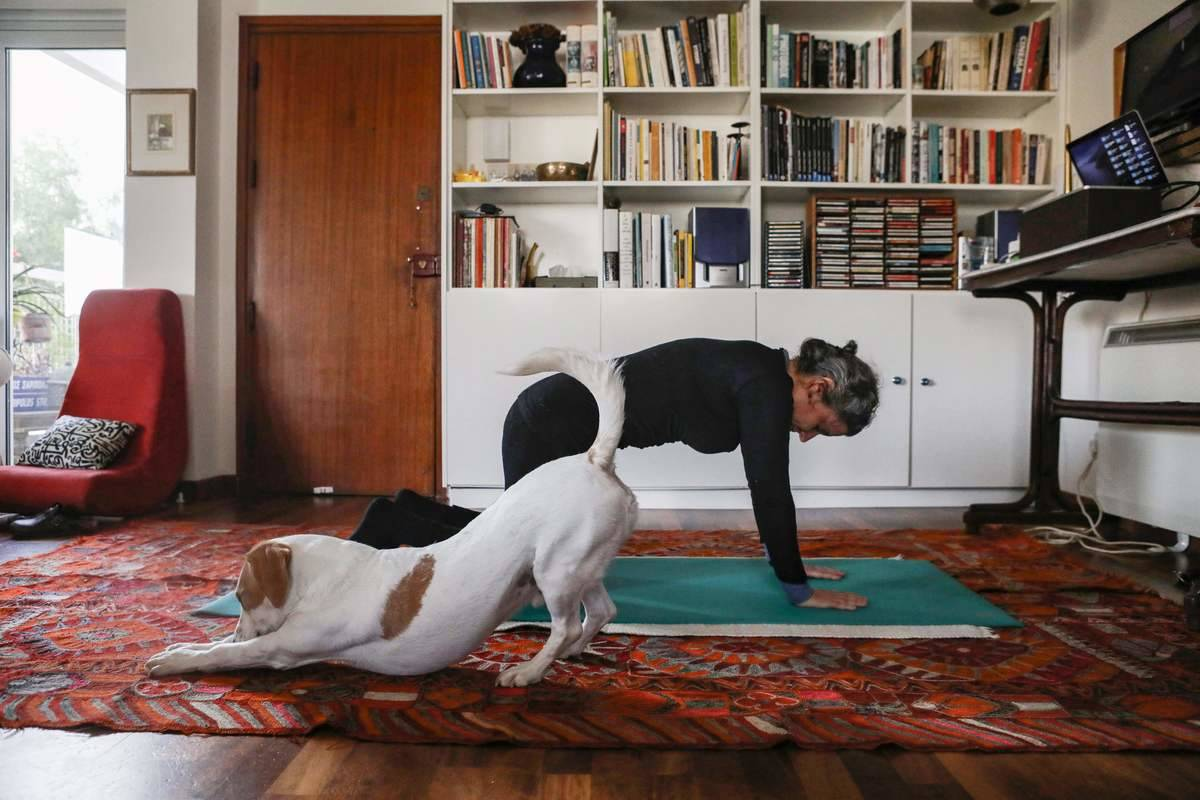 A woman practices yoga indoors with her dog.