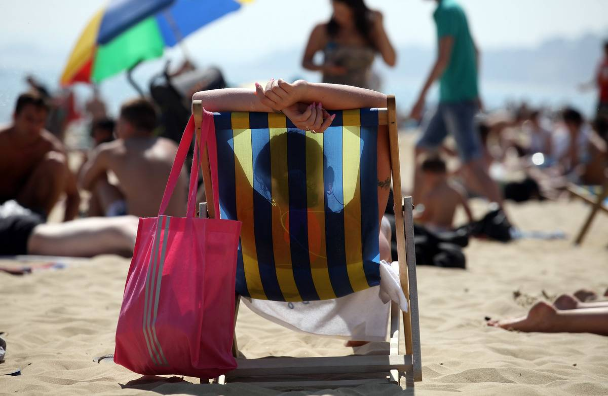 A person sits in a beach chair and sunbathes.