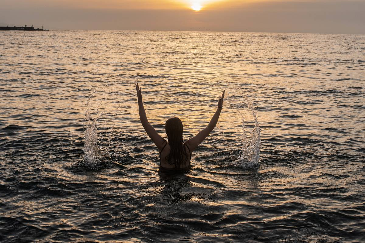 A woman raises her hands above the water as she swims in the ocean during sunset.
