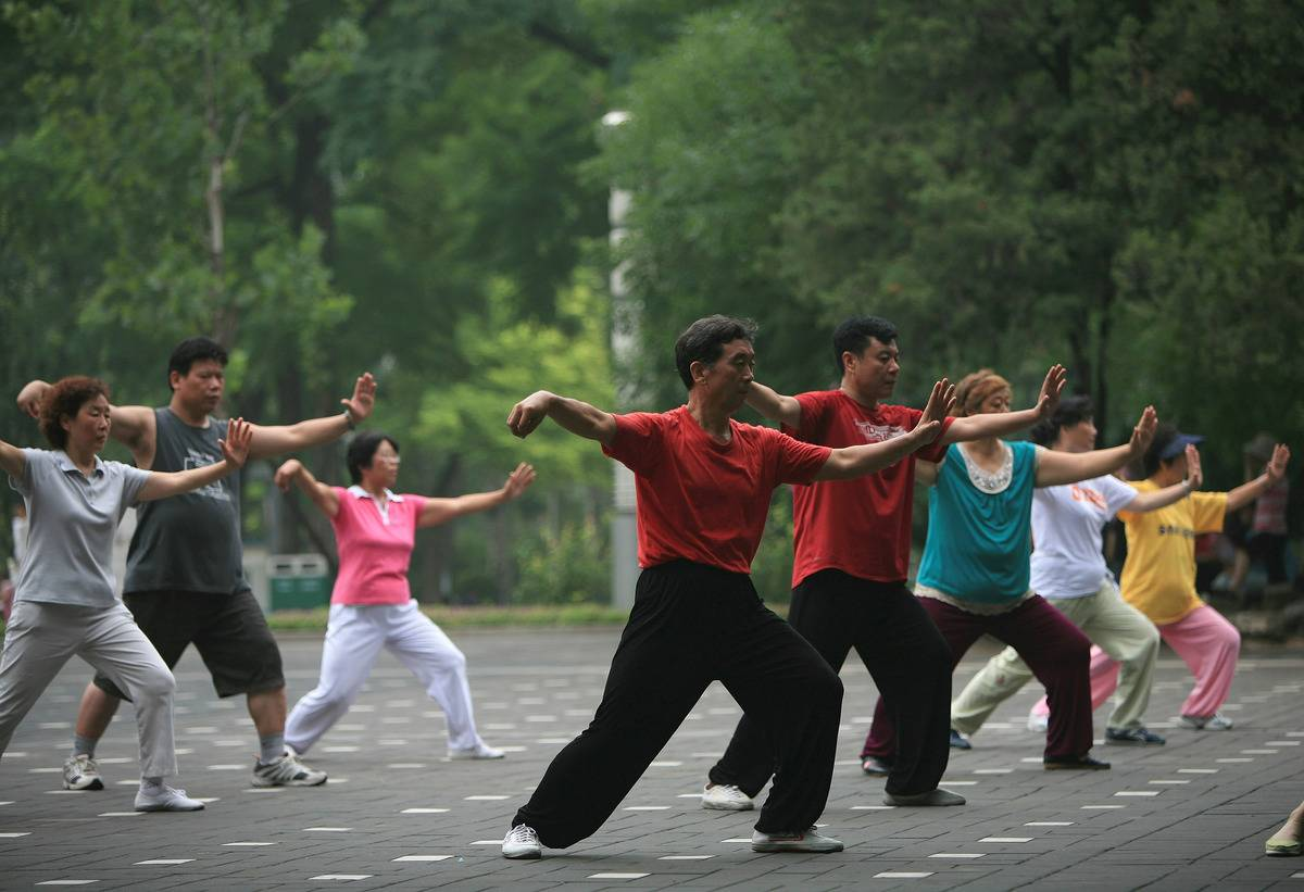 People practice tai chi during a class in a public park.