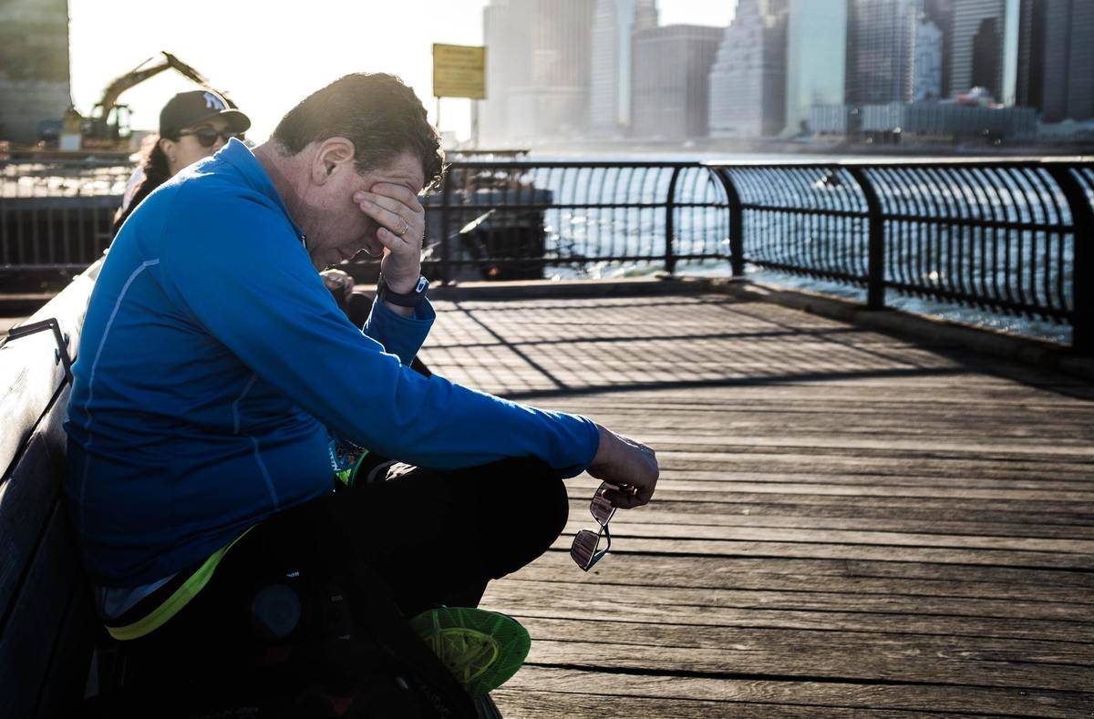 A tired man sits on a bench on a pier.