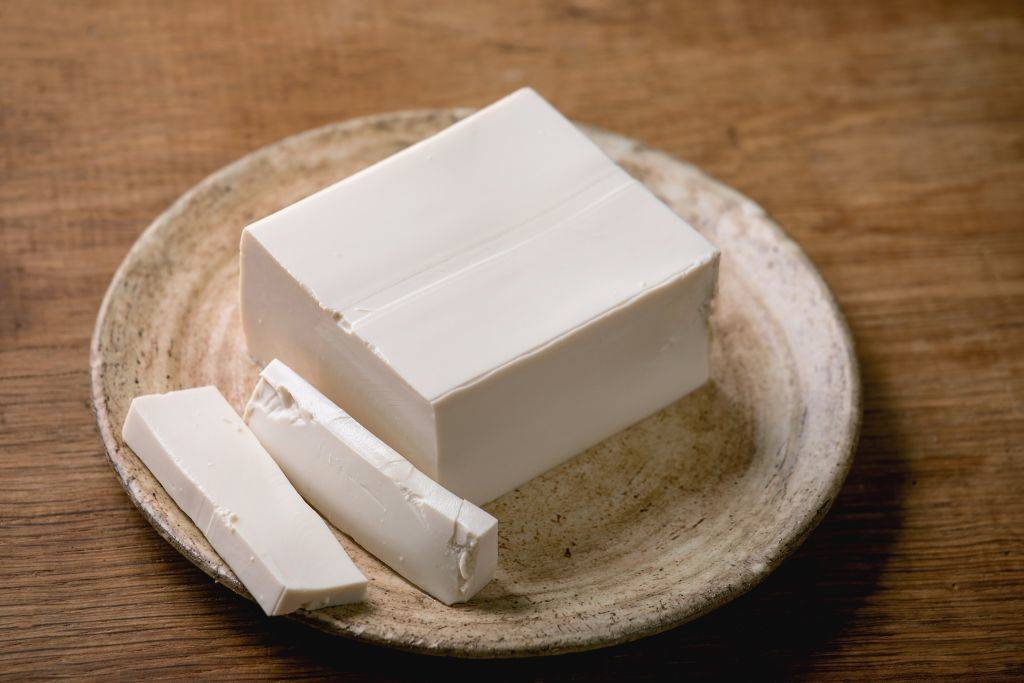 Silk tofu japanese soy cheese whole piece on ceramic plate with chopsticks over wooden table