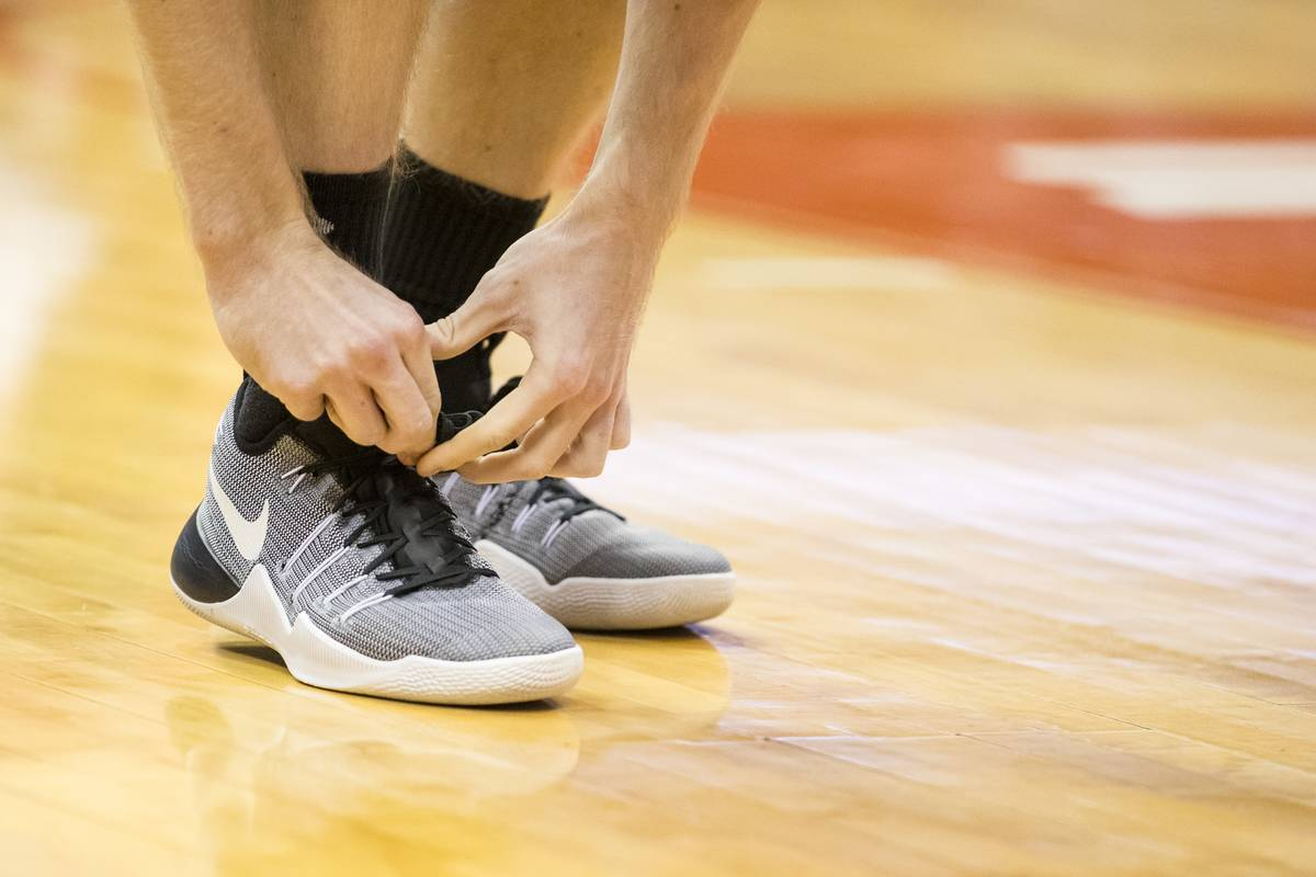 An athlete ties his running shoes.