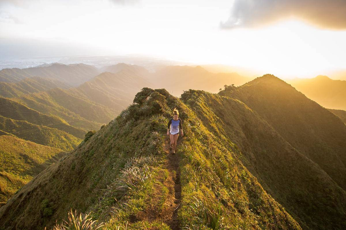 A woman hikes on a trail along mountains.