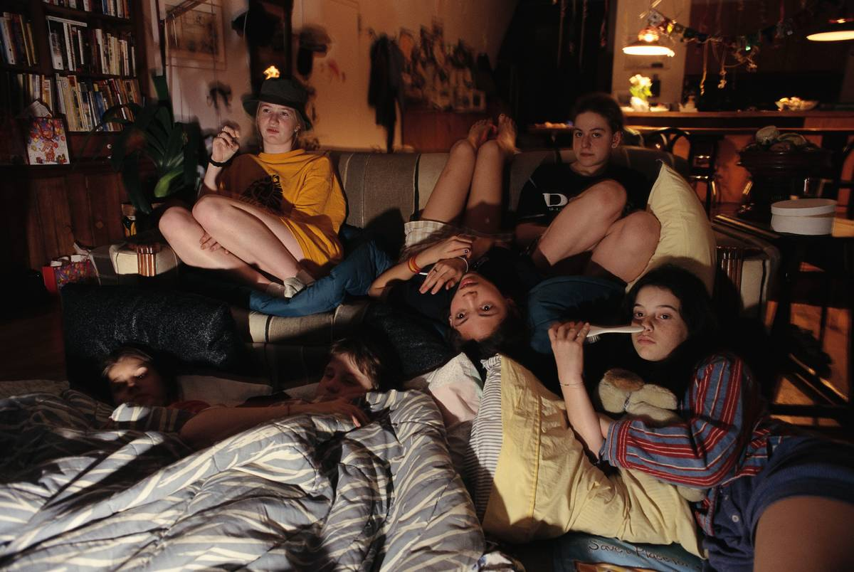 Several women crowd around a couch to watch TV together.