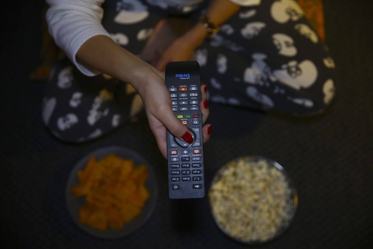 A woman holds a remote while eating snacks from bowls on the floor.