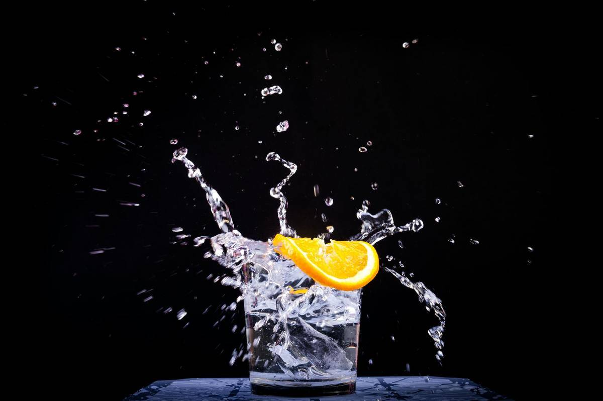 Water splashes in a glass against a black background.