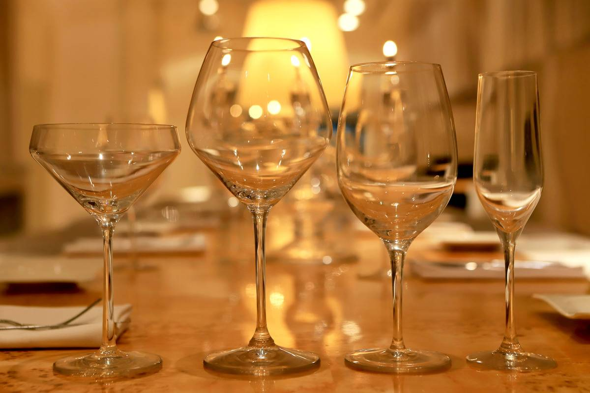 Four empty wine glasses stand in a row on a dinner table.