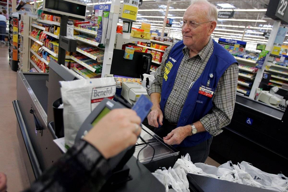 A 72-year-old man works the cash register at Walmart.