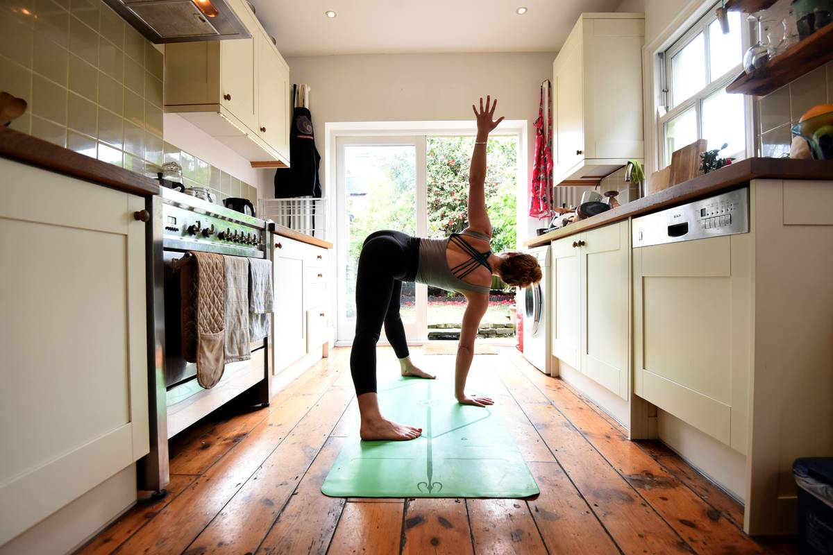 A woman practices yoga in her kitchen.