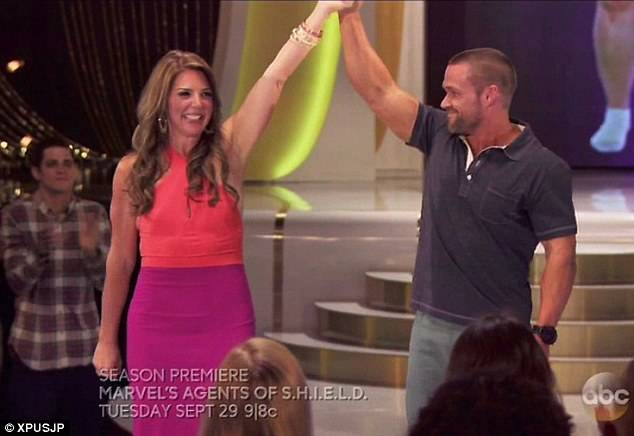 Jackie Rodriguez holds up Chris Powell's hand after losing over 100 pounds.