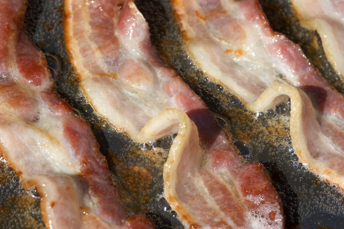 Strips of bacon fry on an electric grittle.