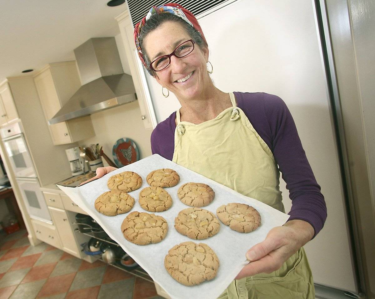 A woman holds up a tray of cookies that she baked.