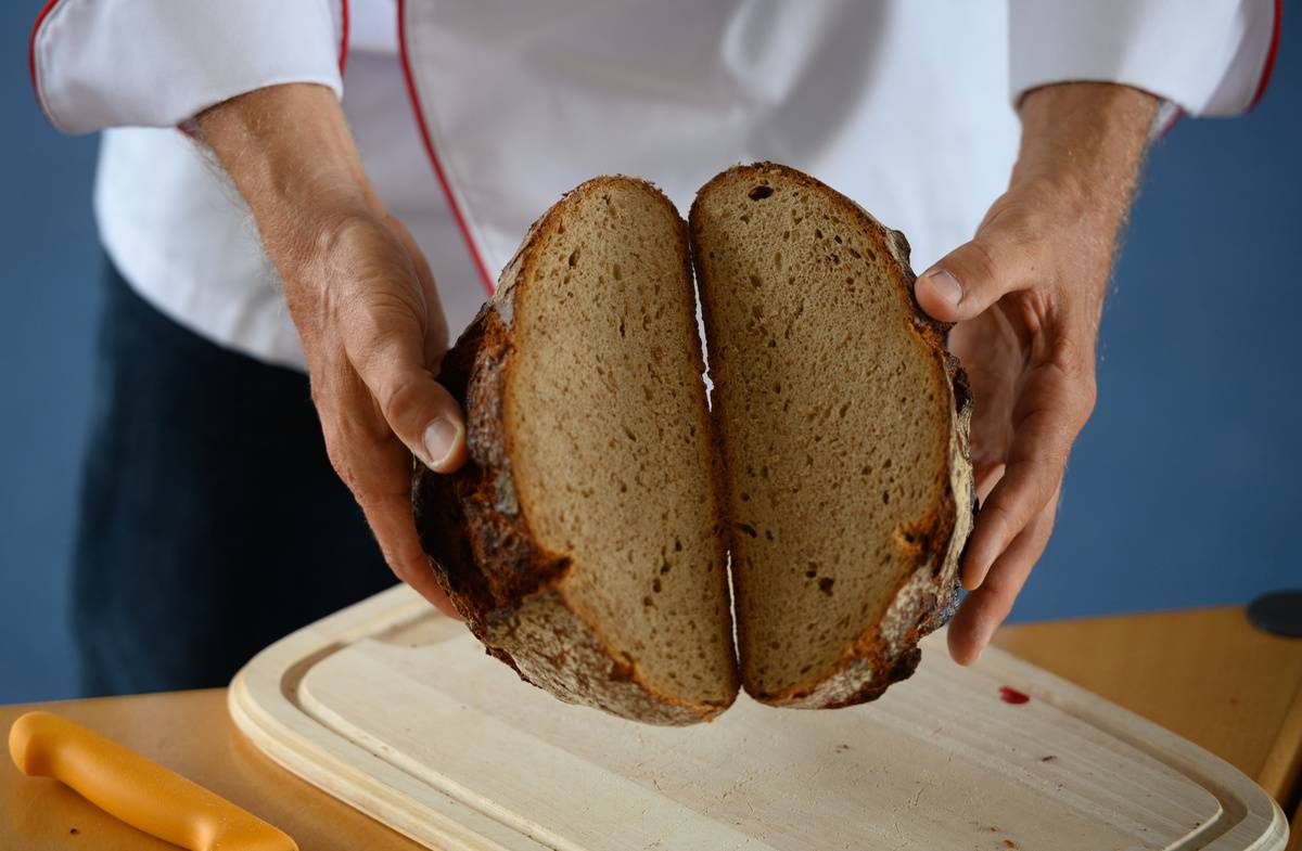 A chef breaks open a loaf of bread.