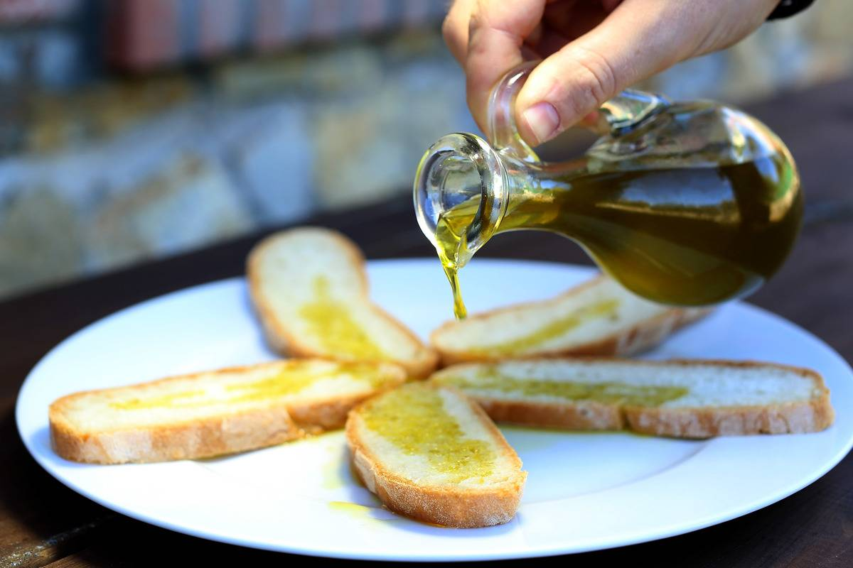 A person pours olive oil on bread.