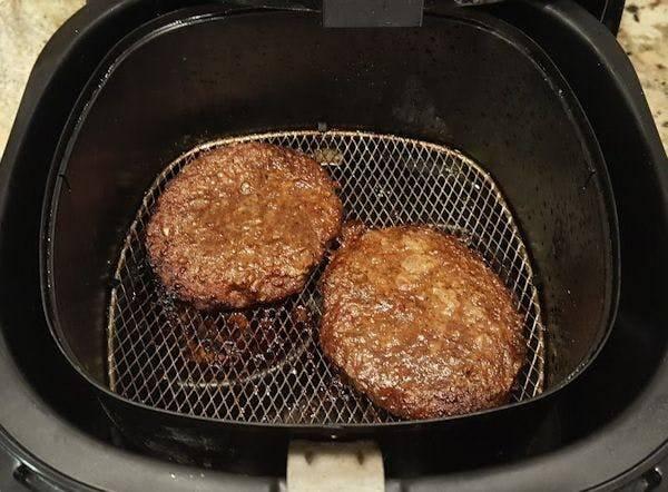 Burger patties cook in an air fryer.