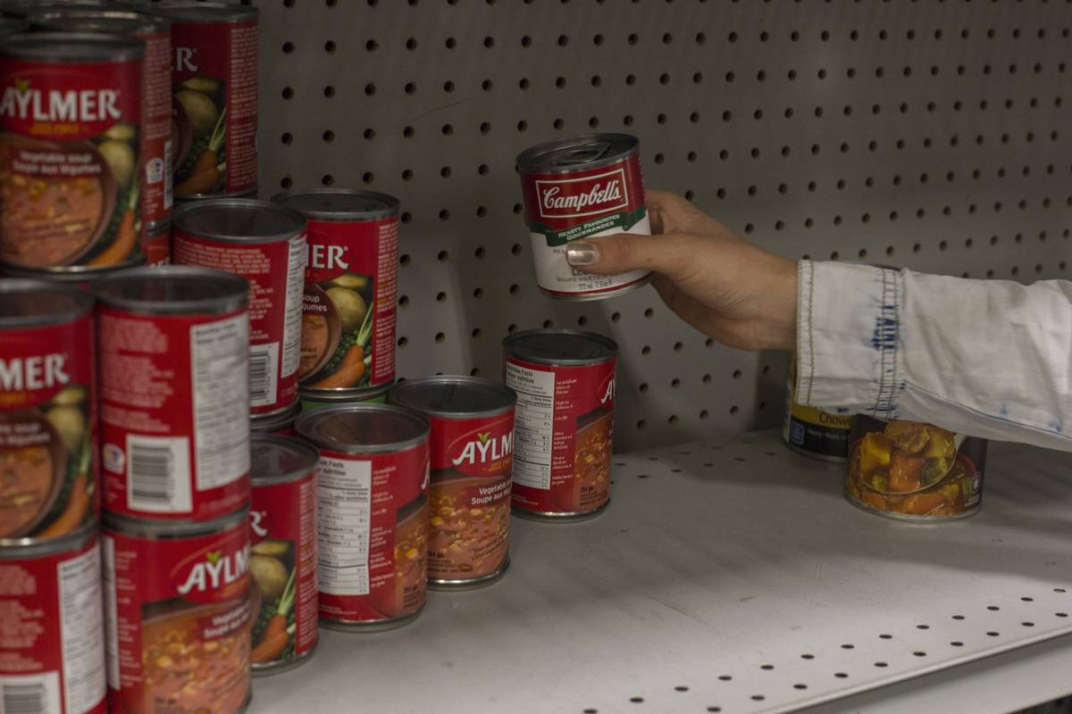 A volunteer stacks shelves with canned soup.