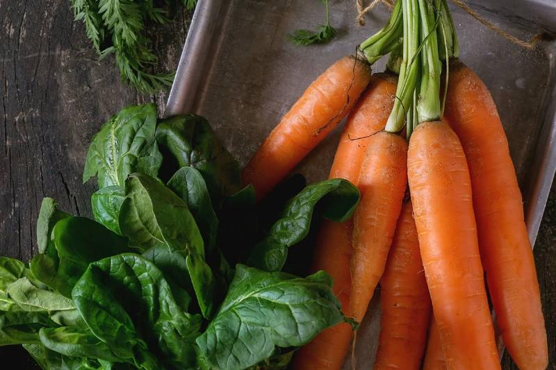Carrots and spinach, two nitrate-heavy vegetables, lie on a baking tray.