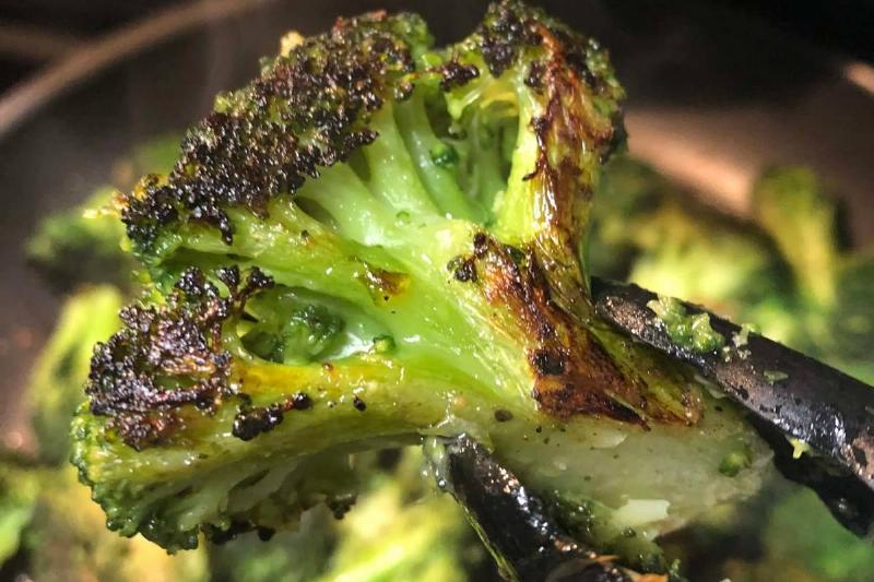 A person holds up charred broccoli with tngs.