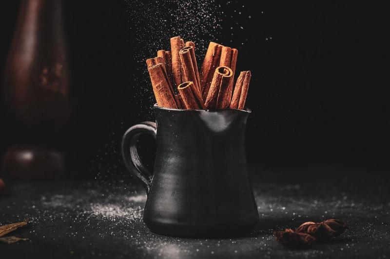 Cinnamon sticks are in a black mug, and powdered cinnamon is sprinkled on it.