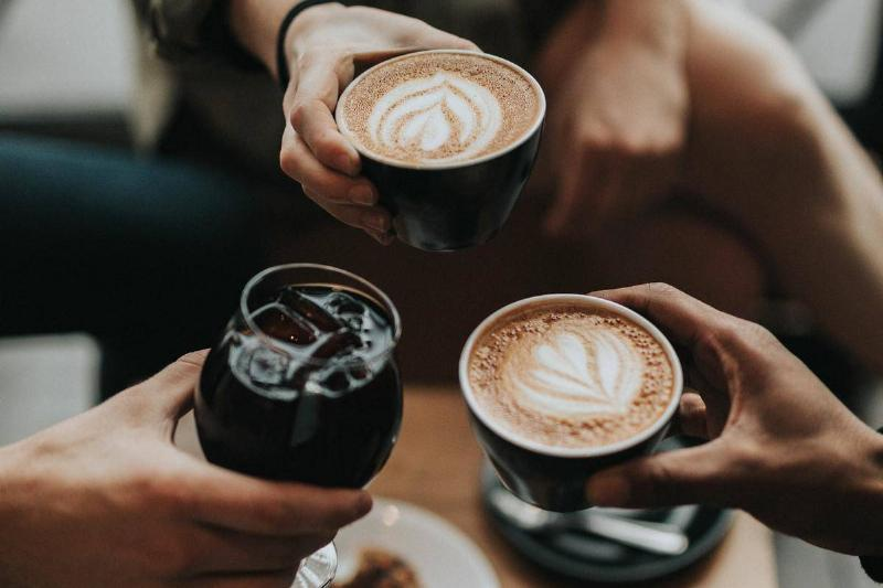 Three customers of a coffee shop hold up their drinks.