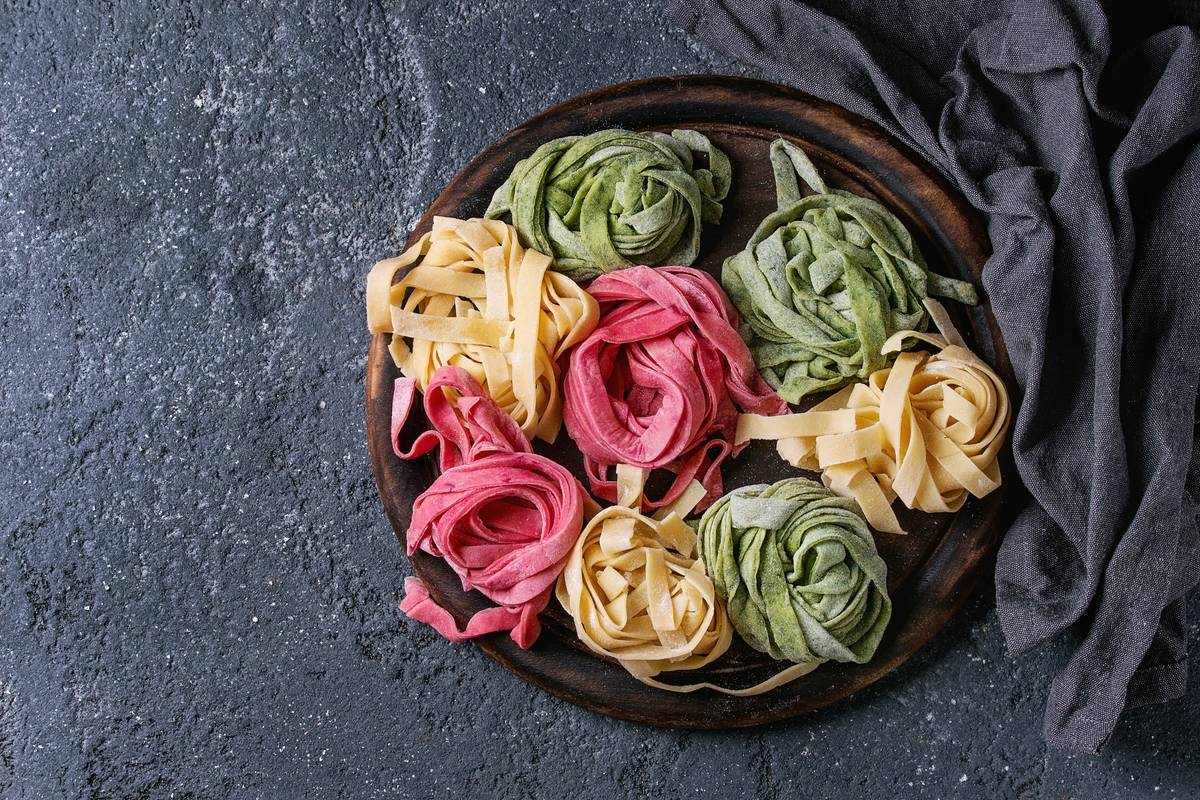 A variety of veggie noodles are twirled and arranged on a plate.