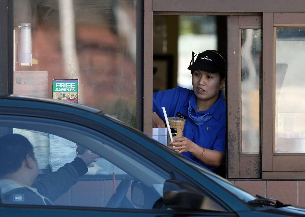 A McDonald's employee hands a customer a drink in a drive thru.