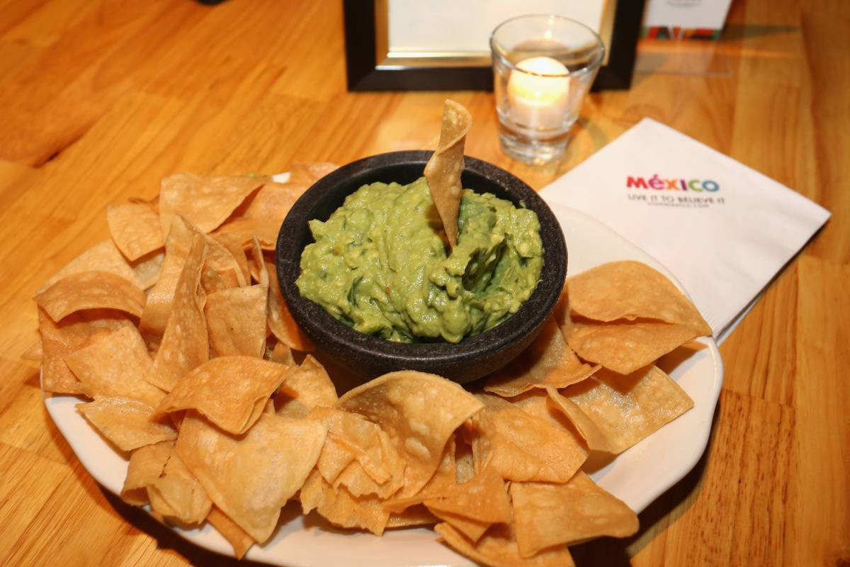 A plate is filled with chips and a bowl of guacamole.