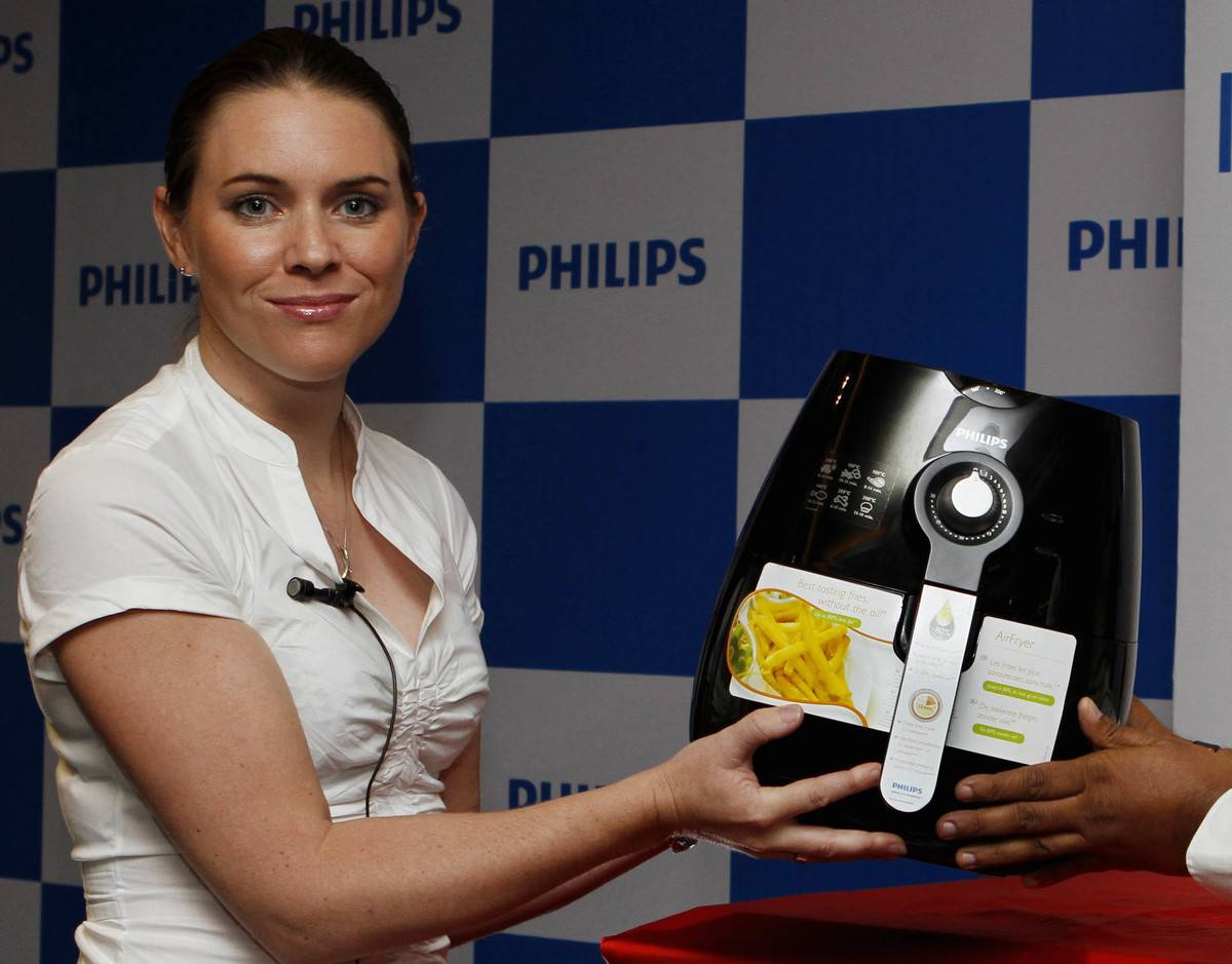 A woman holds up an air fryer during its launch.