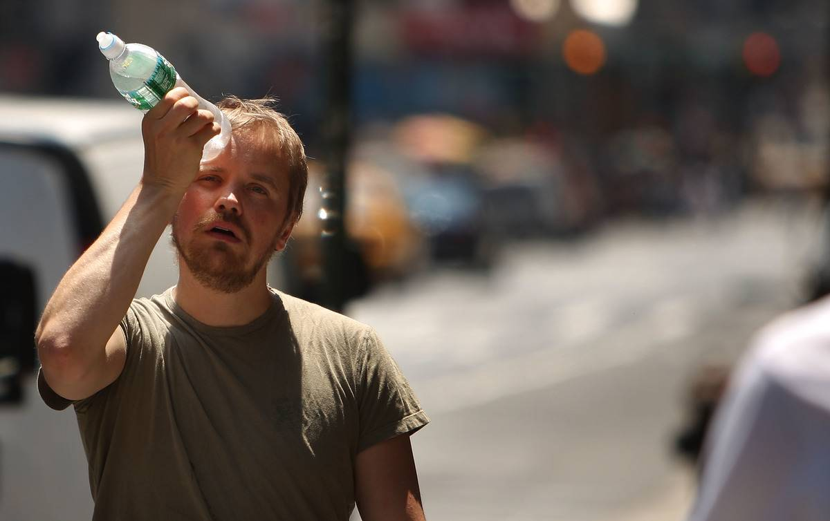 During a hot day, a man holds a cold water bottle to his forehead to cool down.