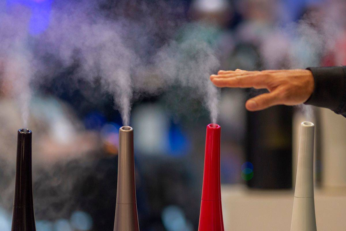 A person holds their hand over humidifiers that are on display at an electronics show.