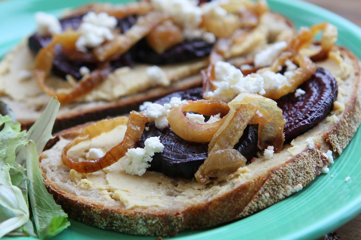 A sandwich includes hummus, roasted onions, beets, and feta.