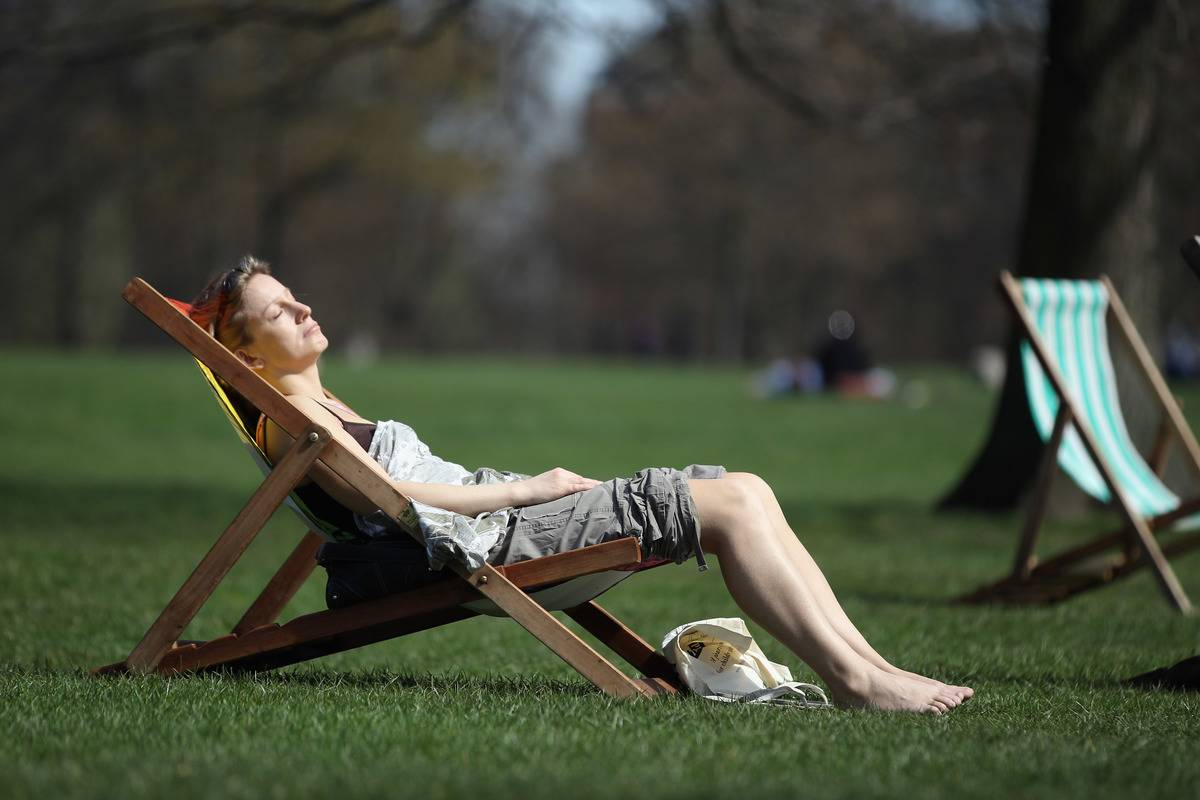 A woman sunbathes on a lawn chair in a London park.