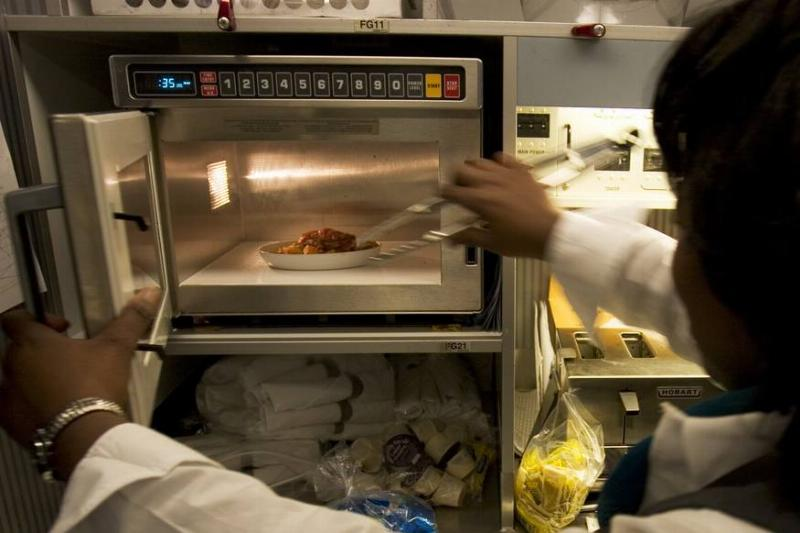 A woman takes leftovers out of a microwave.