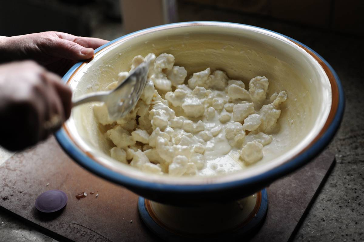 A person stirs around cottage cheese.